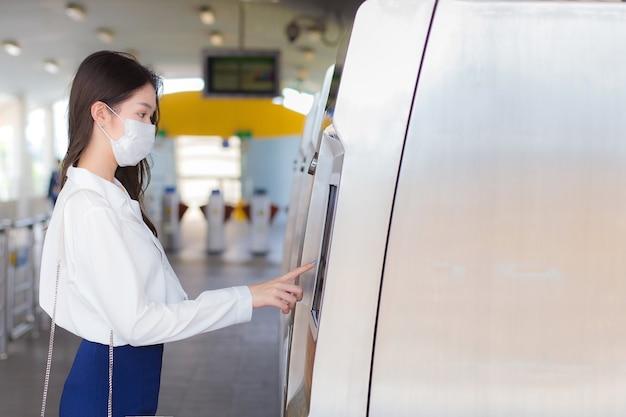 흰 셔츠를 입은 아름다운 젊은 아시아 여성 사업가는 질병 바이러스와 먼지를 방지하기 위해 마스크를 쓰고 pm.2.5 하늘 기차역에 있는 매표기를 눌러 사무실에 출근합니다.