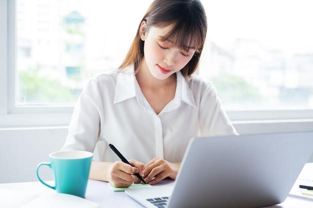 美しい若いアジアの実業家は良い気分でオンラインで働いています