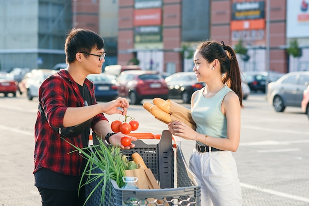 Beautiful young asian couple checking purchased food in the shopping cart near the big store