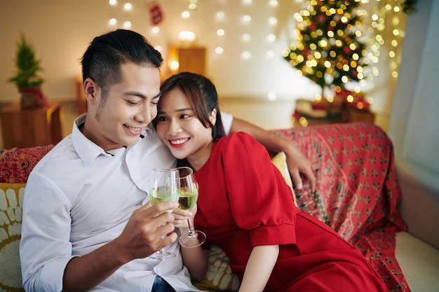 家でクリスマスの夜を過ごし、シャンパンを飲むのが大好きな美しい若いアジアのカップル
