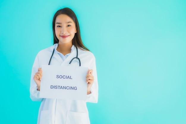 社会的な距離と記号の紙の美しい若いアジア医師女性