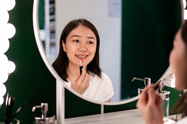 Beautiful young asian ethnicity woman looking herself in the mirror and applying lips gloss on her mouth in dressing room.