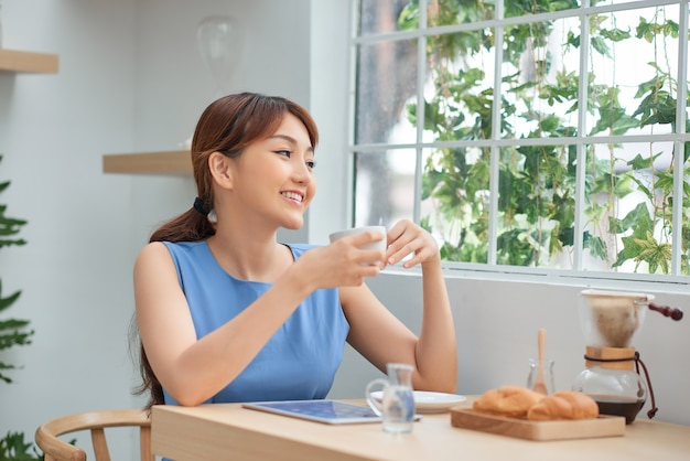 Beautiful young asian girl drinking coffee and using tablet while sitting behind the window