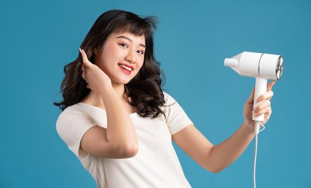 彼女の髪を乾かす美しい若いアジアの女の子