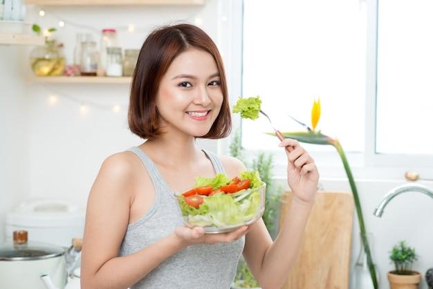サラダを食べる美しい若いアジアの女の子。健康的な食べ物を食べる幸せな女の子の笑顔。