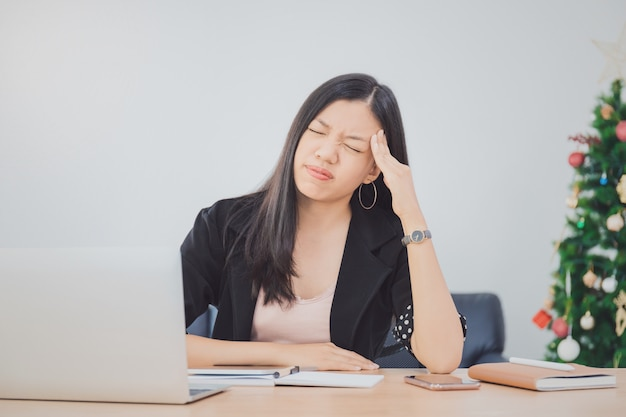 Beautiful young asian girl feeling headache and stress in office space with laptop and decorate christmas tree background