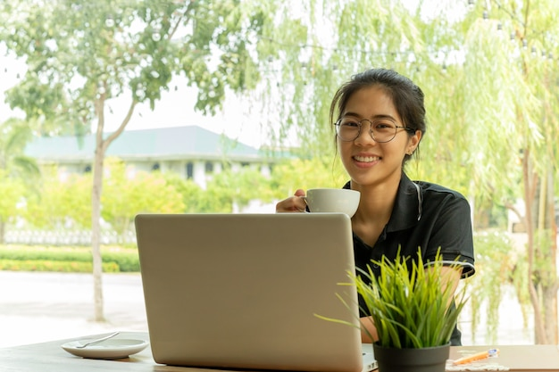 Beautiful young asian girl holding coffee with laptop on the table at cafe.
