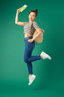 バッグを身に着けて、航空券、緑の上のパスポートを保持しながら空中にジャンプする美しい若いアジアの女の子の旅行者。