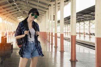 列車の駅で一人で旅行する美しい若いアジアの女の子