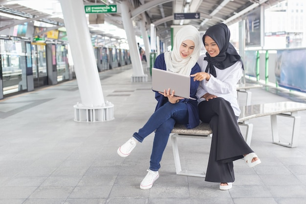 Beautiful young asian girl two person working at a skytrain with a laptop. muslim women