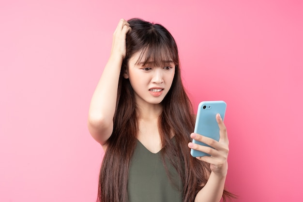 분홍색 벽에 전화를 사용 하여 아름 다운 젊은 아시아 소녀