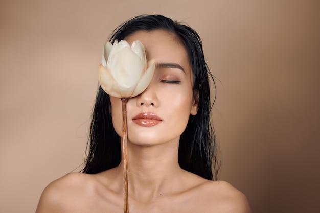 베이지색 배경의 스튜디오에서 자연스러운 화장과 젖은 머리를 한 아름다운 아시아 소녀