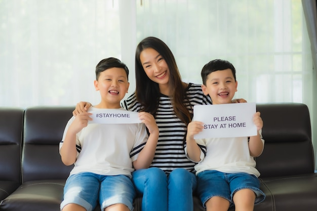 Beautiful young asian mom with her two sons show paper to stay home for protect coronavirus