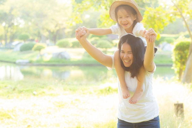 Beautiful young asian mother carrying little daughter with smile