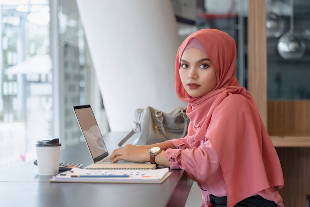 Beautiful young asian muslim business woman in pink hijab and casual wear working with laptop