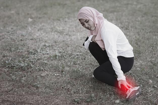 スポーツウェアの美しい若いアジアのイスラム教徒の少女は、長い運動の後、足と痛みに手を保ちます。トレーニング中に問題や事故を抱えているフィットネス女性。医療とスポーツの概念