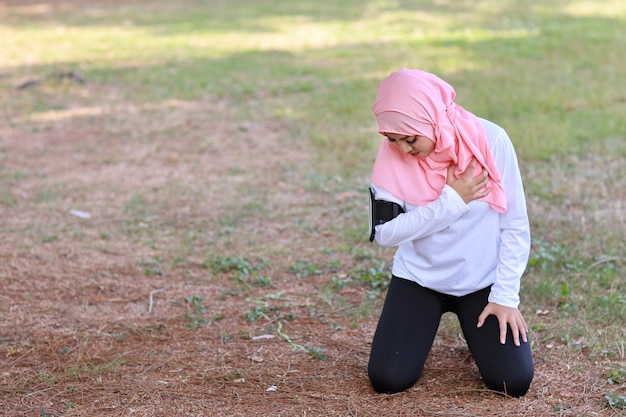 Beautiful young asian muslim girl keeps both hands on chest after long exercise