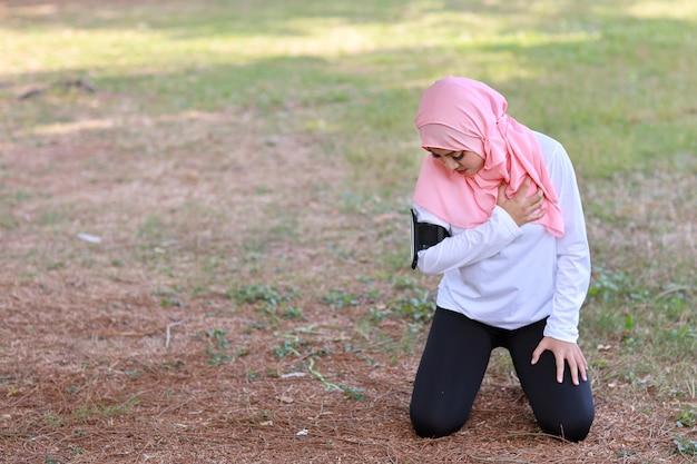 美しい若いアジアのイスラム教徒の少女は、長い運動の後に両手を胸に保ちます