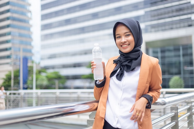 Beautiful young asian muslim with bottled water.