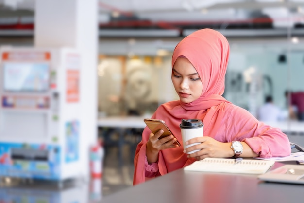 Beautiful young asian muslim woman in pink hijab and casual wear working with laptop and business report at creative co-working.