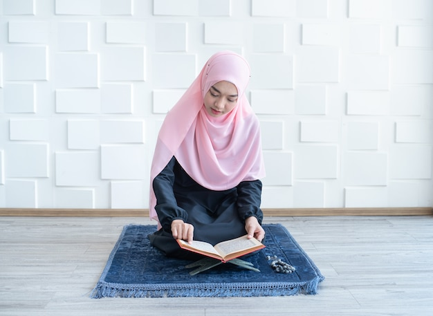 Beautiful young asian muslim woman reading quran