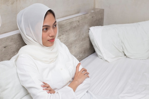 Beautiful and young asian muslim woman  sitting on bedroom