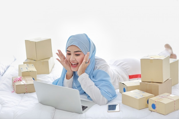 Beautiful and young asian muslim woman in sleepwear with attractive look, lies on bed with computer, mobile phone and online package box delivery. smart girl with hijab receive good news and surprise.