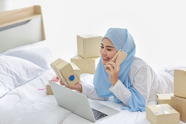Beautiful and young asian muslim woman in sleepwear with attractive look, lies on bed with computer and online package box delivery. startup small business sme freelance woman working with mobile phone