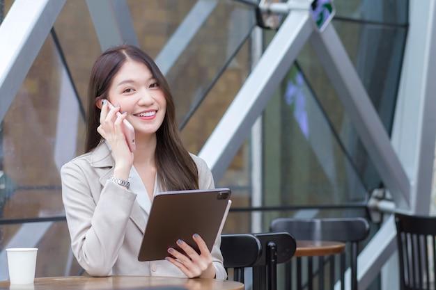 Красивая молодая азиатская профессиональная бизнес-леди в кремовом костюме держит смартфон, чтобы с удовольствием разговаривать, болтать и записывать информацию на планшете, находясь в кафе.