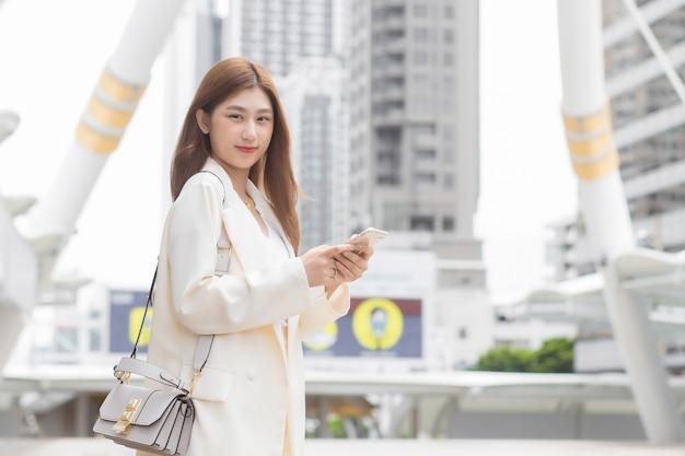 クリーム色のスーツを着た美しい若いアジアのプロの働く女性は、彼女がビジネスビルのあるオフィスで働くために屋外を歩いている間、パートナーと連絡を取るために携帯電話(スマートフォン)を使用しています。