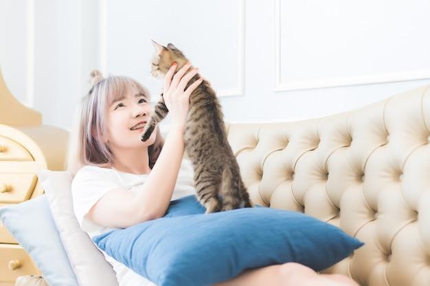美しい若いアジアのタイの女性は彼の猫と一緒にソファーで横になっていて、リビングルームで愛で猫の頭をなでていました
