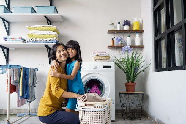 美しい若いアジアの女性と子供の女の子の小さなヘルパーは家で洗濯をしています。