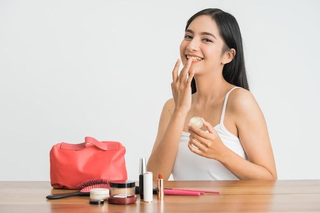 그녀의 얼굴에 화장품 크림을 적용하는 아름 다운 젊은 아시아 여자. 립밤