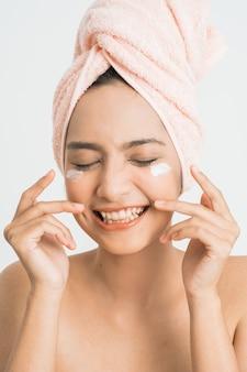 Красивая молодая азиатская женщина, наносящая косметический крем на лицо