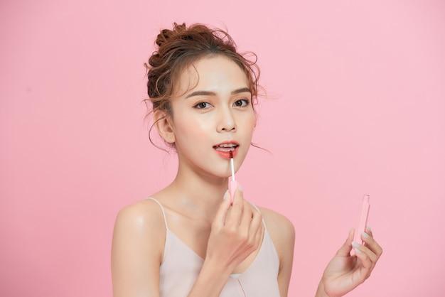 ピンクの背景に分離された口紅を適用する美しい若いアジアの女性。