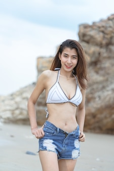 Beautiful young asian woman in bikini relaxing on sand beach,travel outdoor summer vacation concept