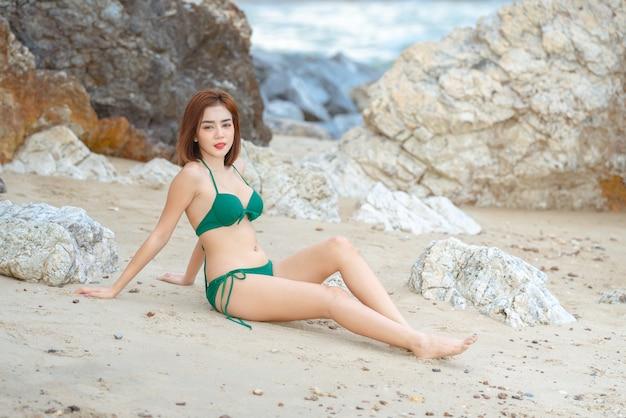Beautiful young asian woman in bikini relaxing on sandy beach