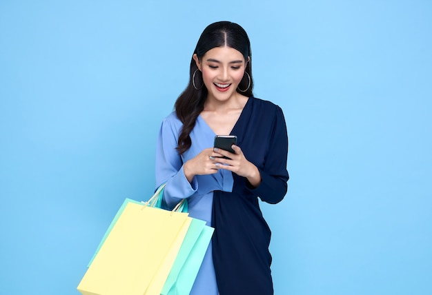 Beautiful young asian woman carrying bags shopping online with smartphone isolated on blue background.
