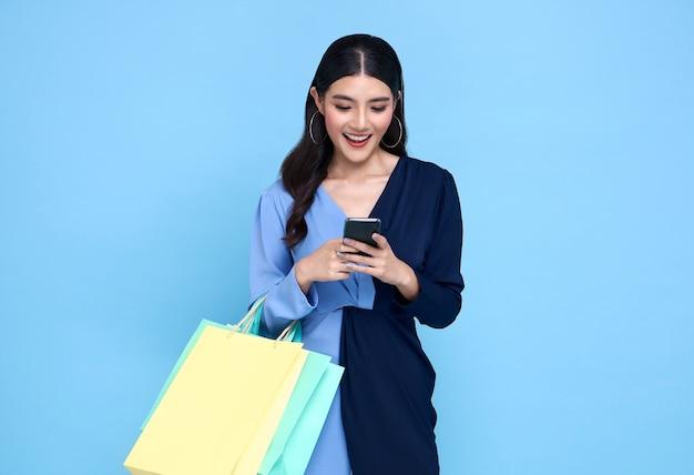 Красивая молодая азиатская женщина, носящая сумки, делая покупки онлайн с смартфоном, изолированным на синем фоне.