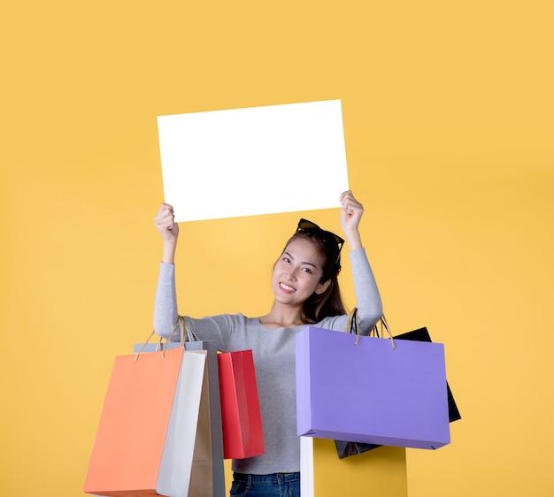 ショッピングバッグを運ぶ美しい若いアジアの女性と黄色の背景で隔離のコピースペースと白いバナーを保持します。