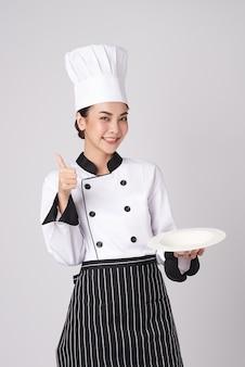 흰색 바탕에 빈 흰색 접시를 들고 있는 아름다운 젊은 아시아 여성 요리사.
