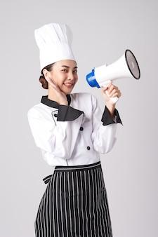 メガホンを保持している美しい若いアジアの女性シェフ。