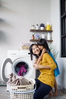 Beautiful young asian woman and child girl little helper are doing laundry at home.