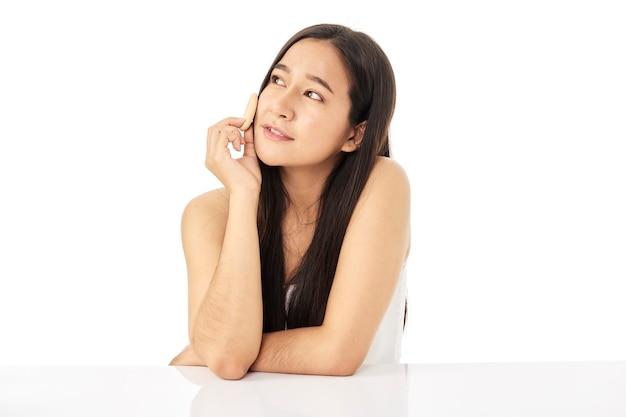 Красивая молодая азиатская женщина очищает лицо красоты, используя ватные диски, очищающий лосьон и тоник для лица для удаления макияжа. у красивой девушки красивая кожа лица. концепция ухода за кожей.