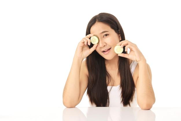 Красивая молодая азиатская женщина очищает лицо красоты, используя очищающий лосьон ломтиков огурца и тоник для лица для удаления макияжа. у красивой девушки красивая кожа лица.