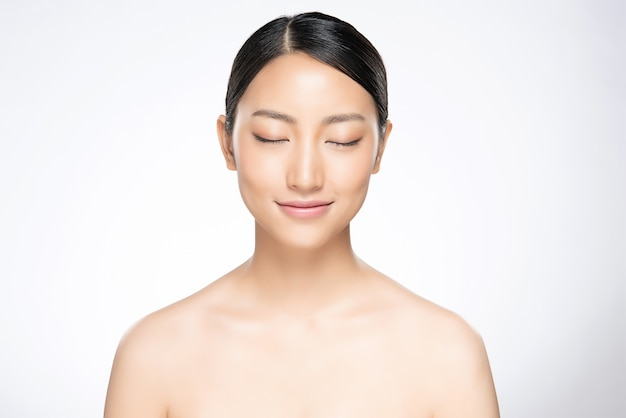 美しい若いアジアの女性は彼女の目を閉じて清潔で新鮮な肌、