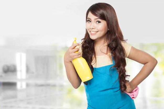 黄色の噴霧器を保持している家事をしている美しい若いアジア女性