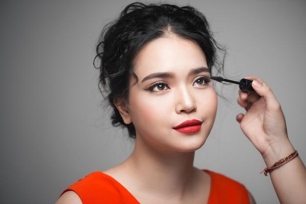 彼女のまつげにマスカラを使用して化粧をしている美しい若いアジアの女性