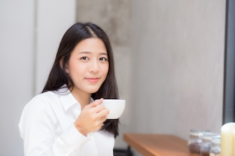 Beautiful  young asian woman drinking coffee and smile in the morning at cafe