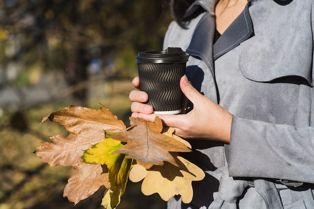 Beautiful young asian woman drinking hot drink from disposable paper cup outdoors in pretty autumn foliage.